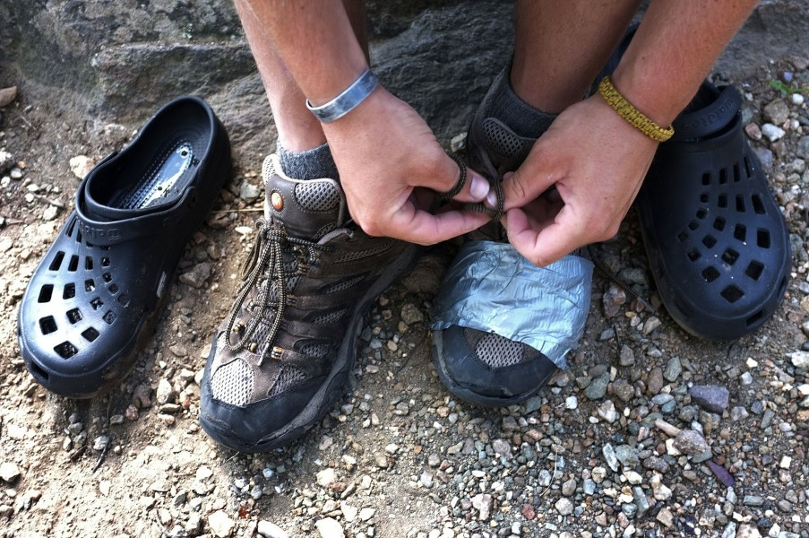 a hiker ties his shoes that have been repaired with duct tape