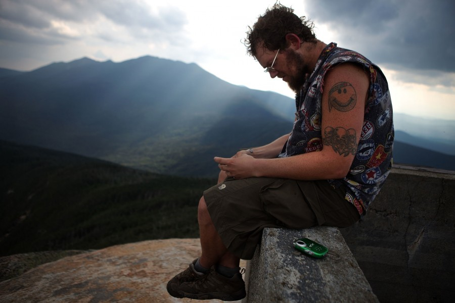 Wes 'Bearbait' Mayeux checks his cellphone for reception on a mountian top in the Whites of New Hampshire