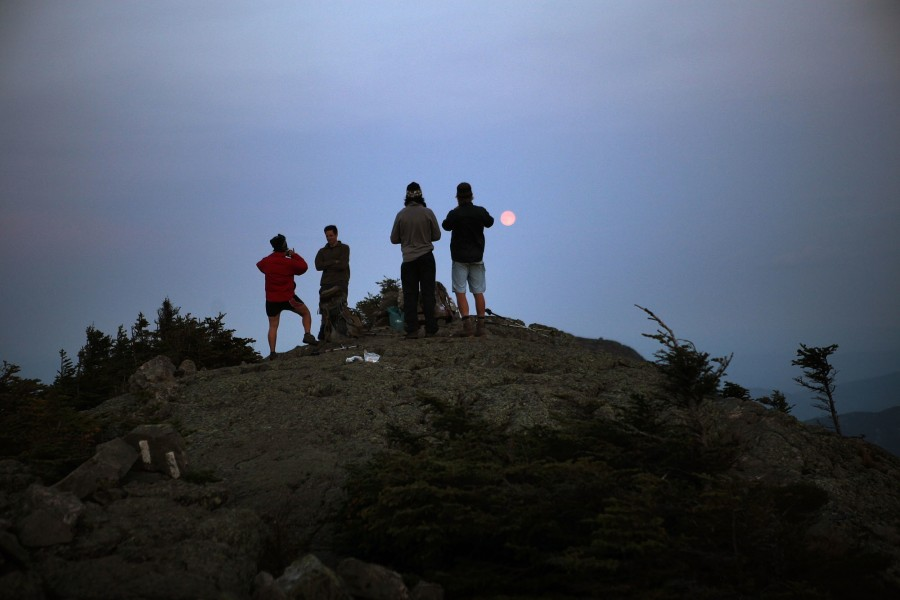 hikers watch the moon rise from a mountaintop in maine along the appalachian trail