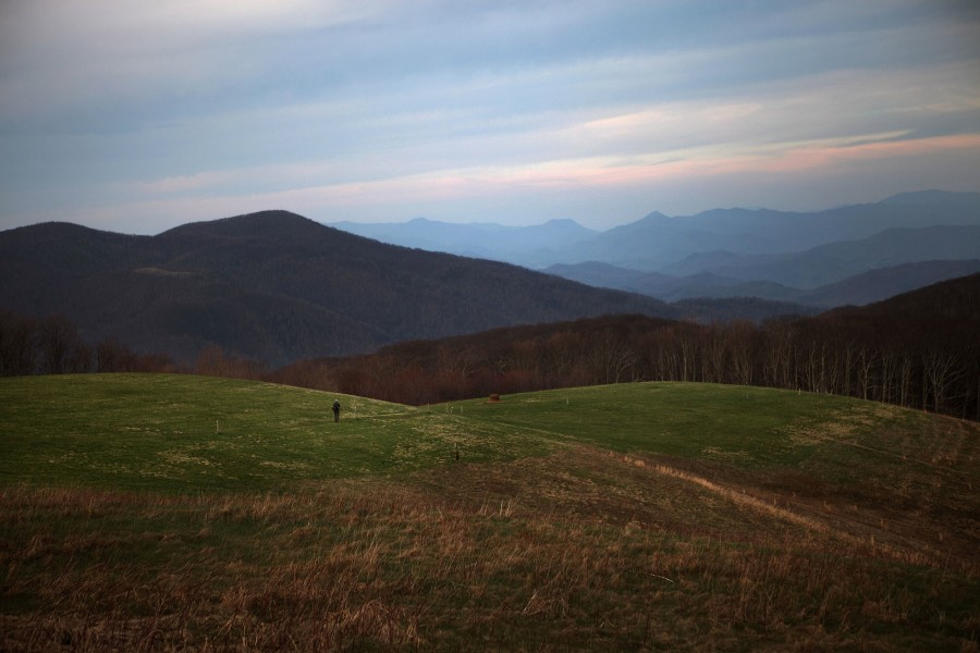 a thru-hiker on the AT crosses max patch, a famous mountain in north carolina