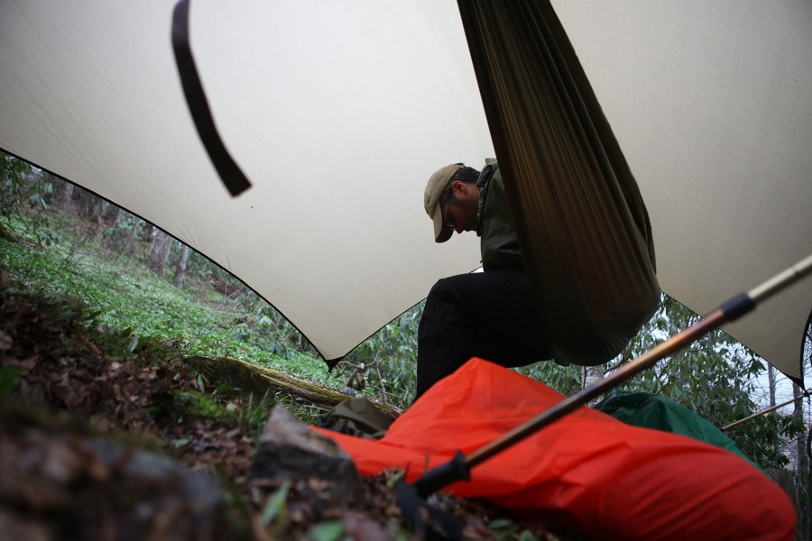 patrick muldoon mckenna sits in his hammock under a tarp along the appalachian trail