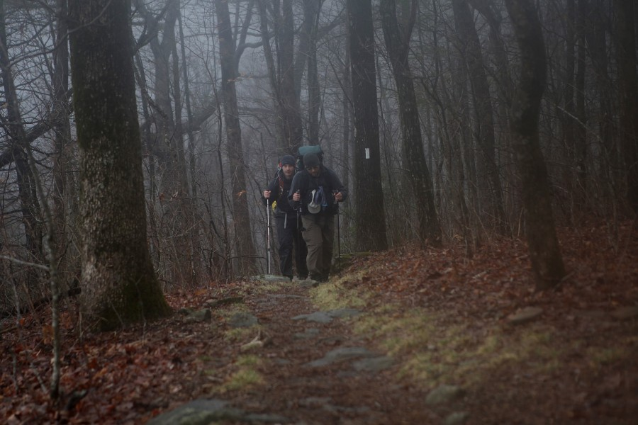 two appalachian trail thru-hikers climb a mountain in georgia in the fog and mist in spring