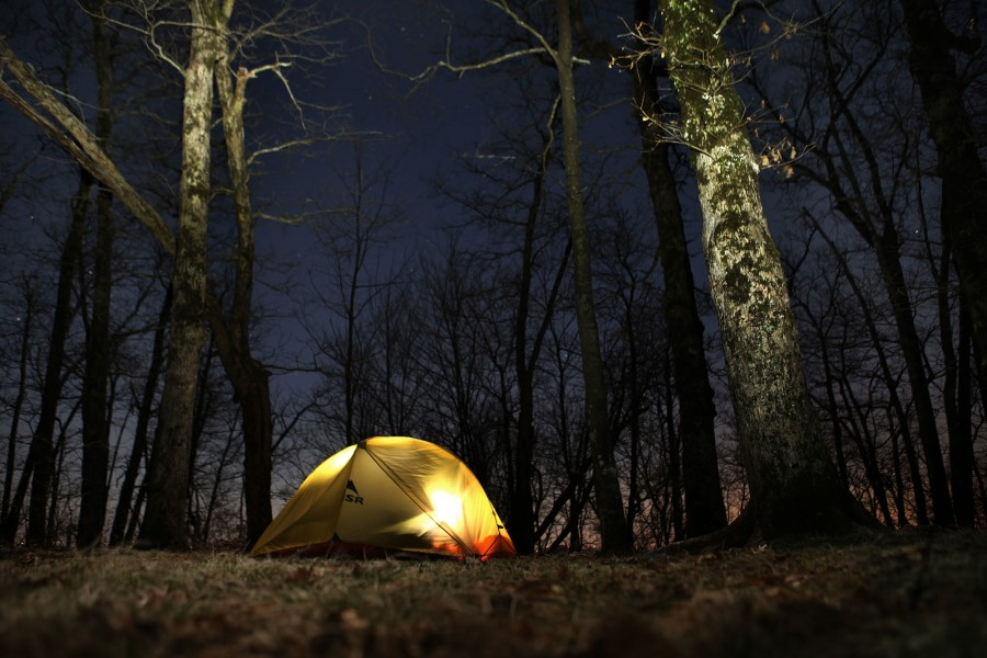 a camper in his tent lights up the fabric with his headlamp at night on the appalachian trail
