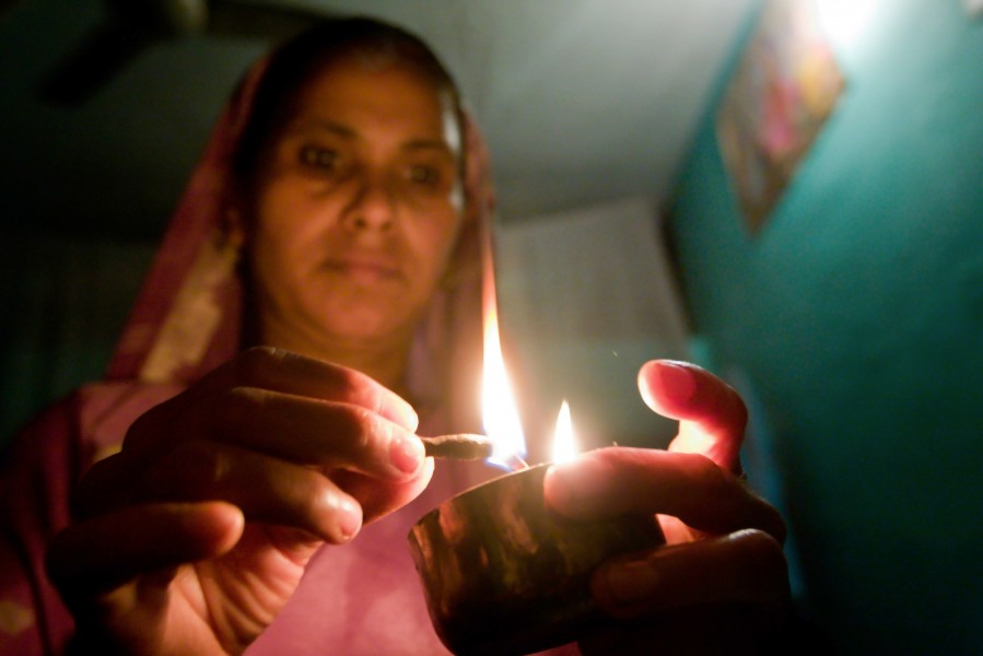 Gudi lights incents before praying in her home
