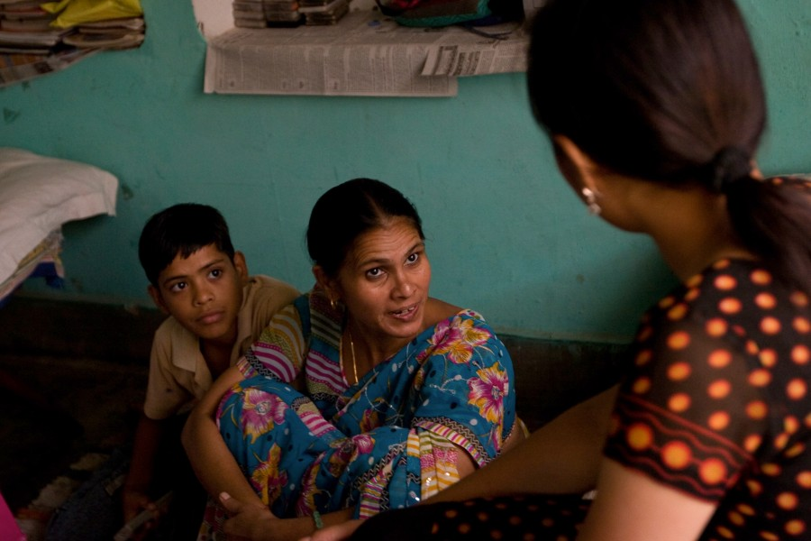 Gudi speaks with her children in their home