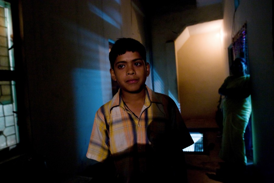 Gudi's son plays in the hallway of their apartment building in New Dehli India