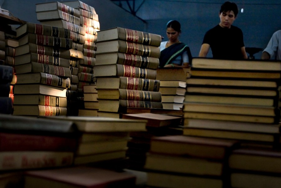 Gudi works behind a stack of books waiting to be polished