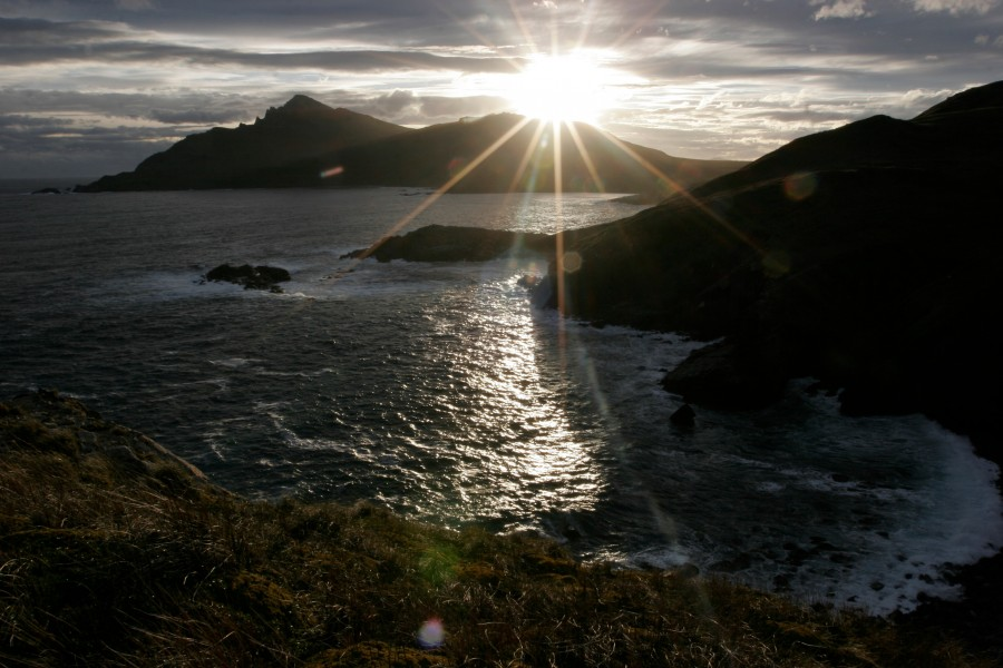 Waves from the Souther Ocean break on the rocks of Cape Horn as the the sun sets in Chile