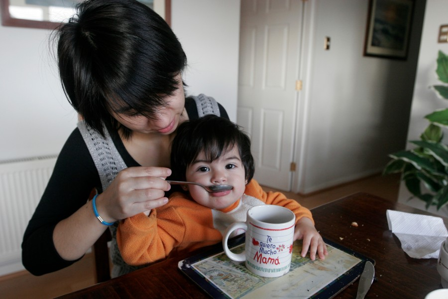 Veronica Heredia feeds her youngest daughter at the kitchen table in the lighthouse where they live.