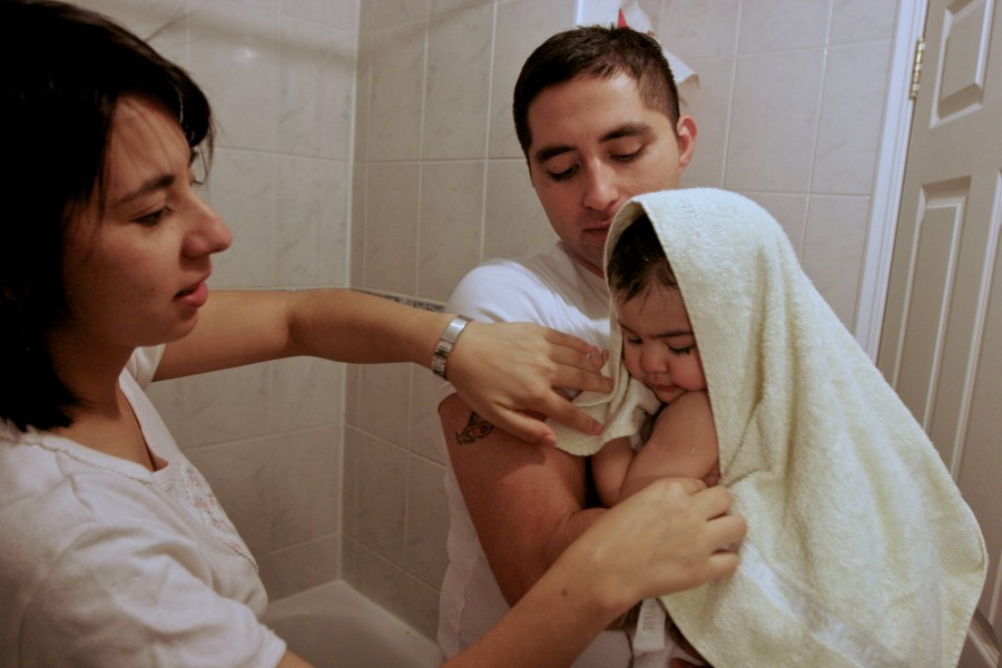Carlos Heredia, and his wife Veronica give their youngest daughter a bath.