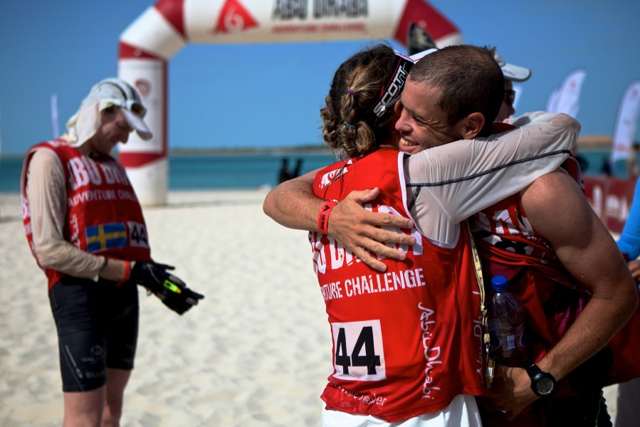 Adventure racers embrace on the beach at the Corniche in Abu Dhabi after finishing the Abu Dhabi Adventure Challenge, a race including trail running, mountain biking and sea kayaking.