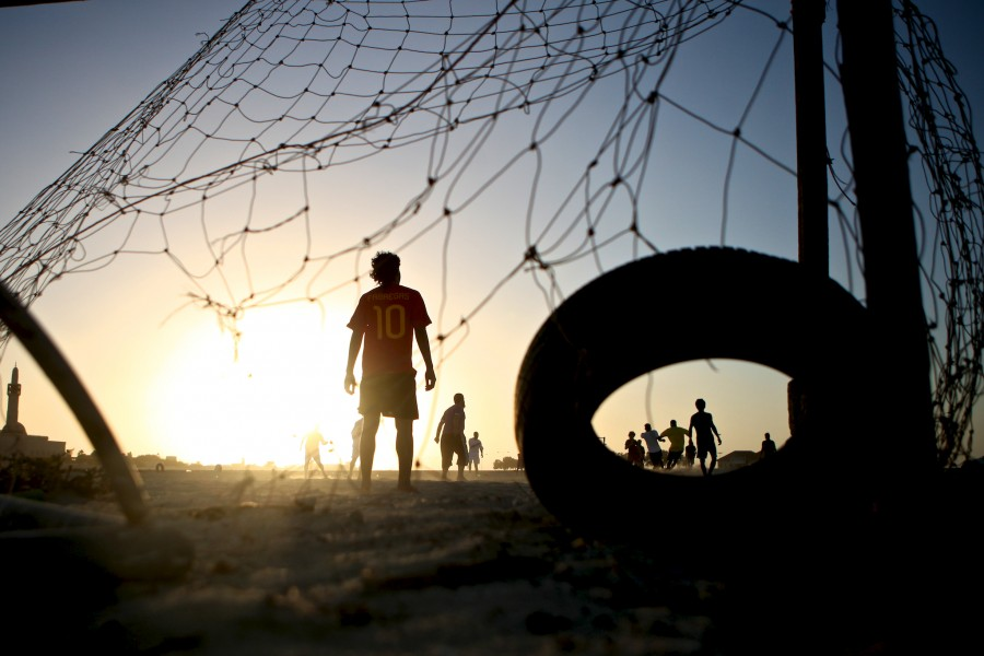 A goalie stands in net as play unfolds upfield during a neighborhood game of football (soccer) in a sand lot outside a town in Umm Al Quwain, United Arab Emirates.