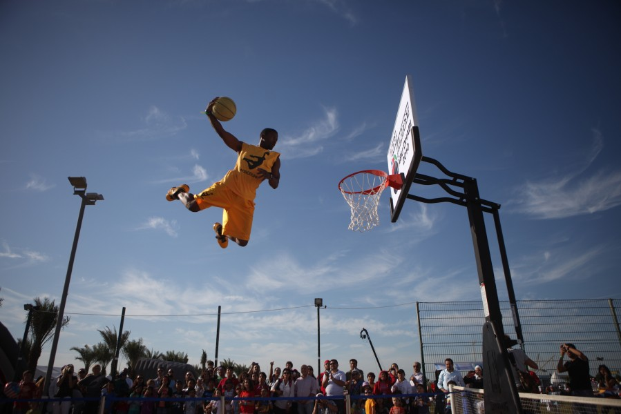 A basketball player dunks the ball in a performance for fans at a festival