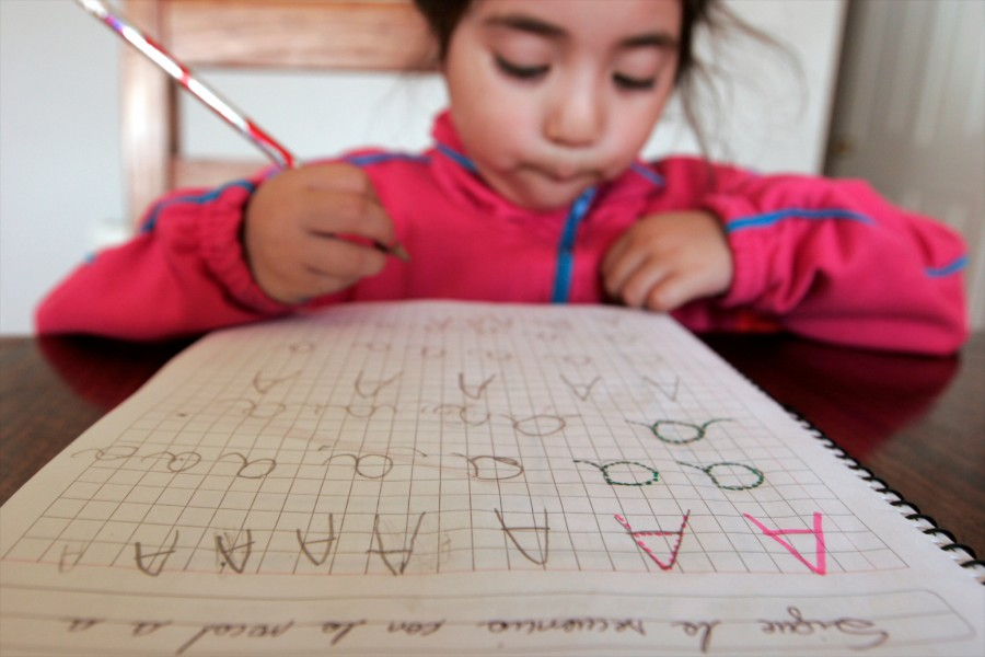 Valentina Heredia is home schooled and practices her letters on the kitchen table of her family's home on Cap Horn, Chile. The family operates the lighthouse and navy station and are the only inhabitants on the island .
