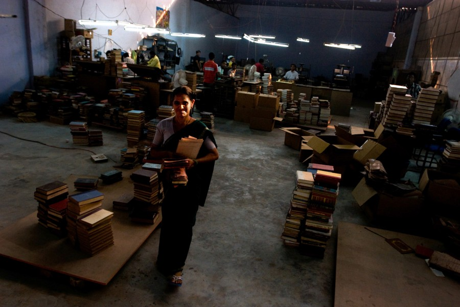 Gudi Davi takes finished books to another station in the factory where she works in New Delhi India