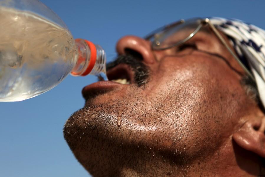 A palestinian farmer drinks from a reused water bottle as he works in the fields.