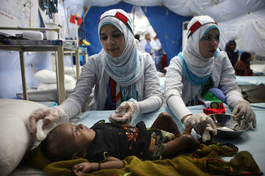 Doctors care for an infant girl who is suffering from a severe fever at a UAE medical clinic in Thatta, Pakistan.
