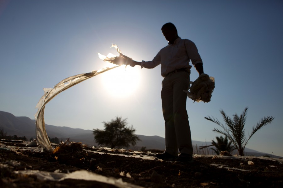 A farmer pulls plastic from the dusty soil in his field in Palestine.