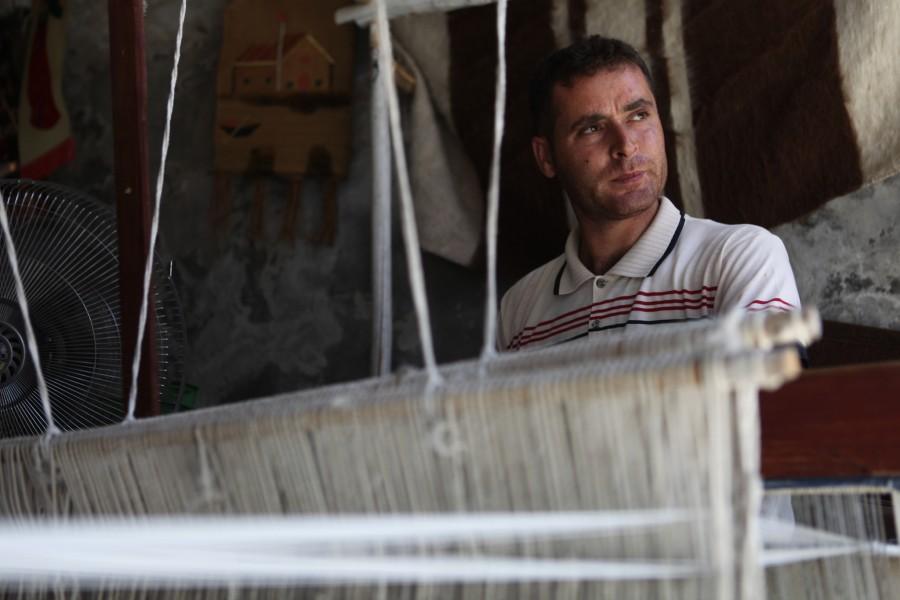 Mehmet Nuri Aydinweaves a wool carpet in his store in Hasenkeyf ,Turkey.