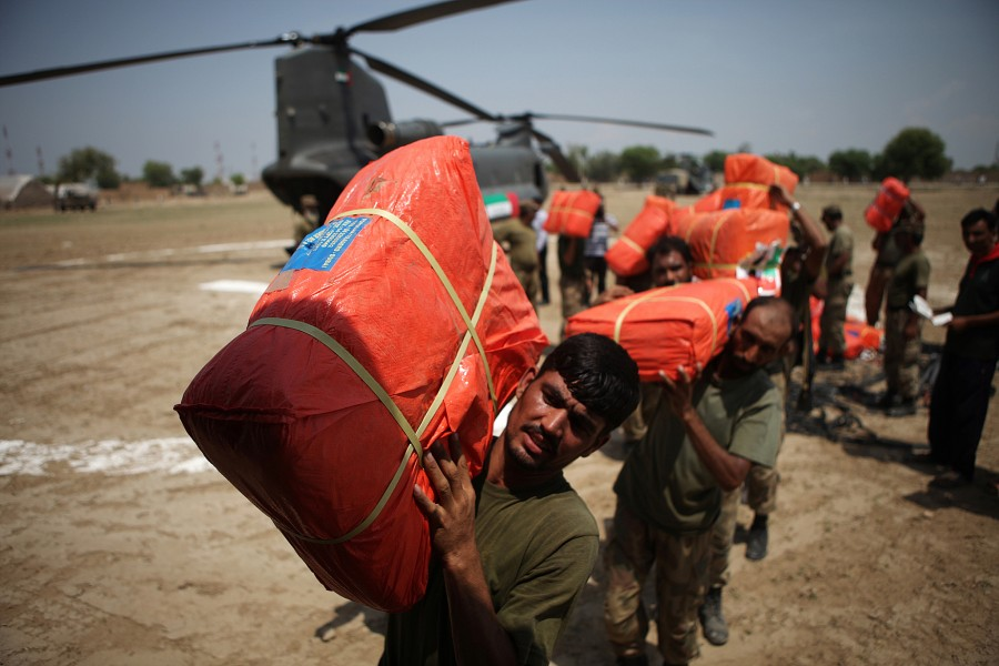 Pakistani military load UAE donate goods on to a truck after it was brought by UAE Chinooks.