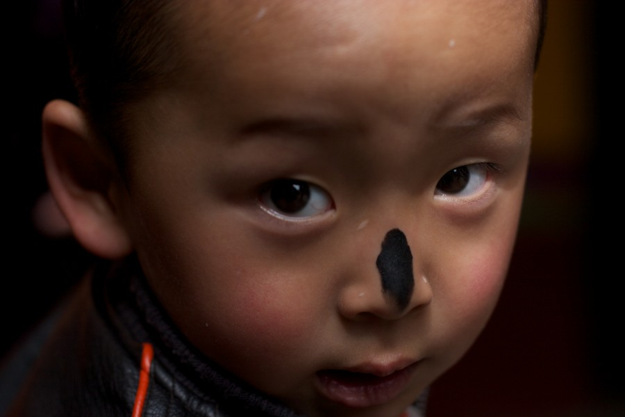 A boy's nose is marked with ash in a religious ceremony in Lhasa, Tibet.