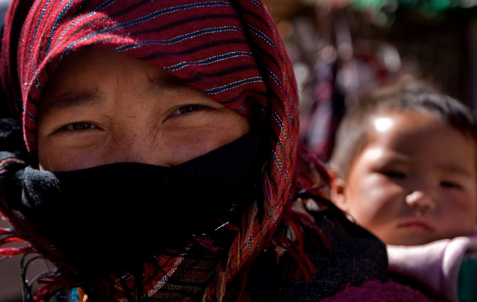 A mother carries her child on her back through the markets of Lhasa, Tibet