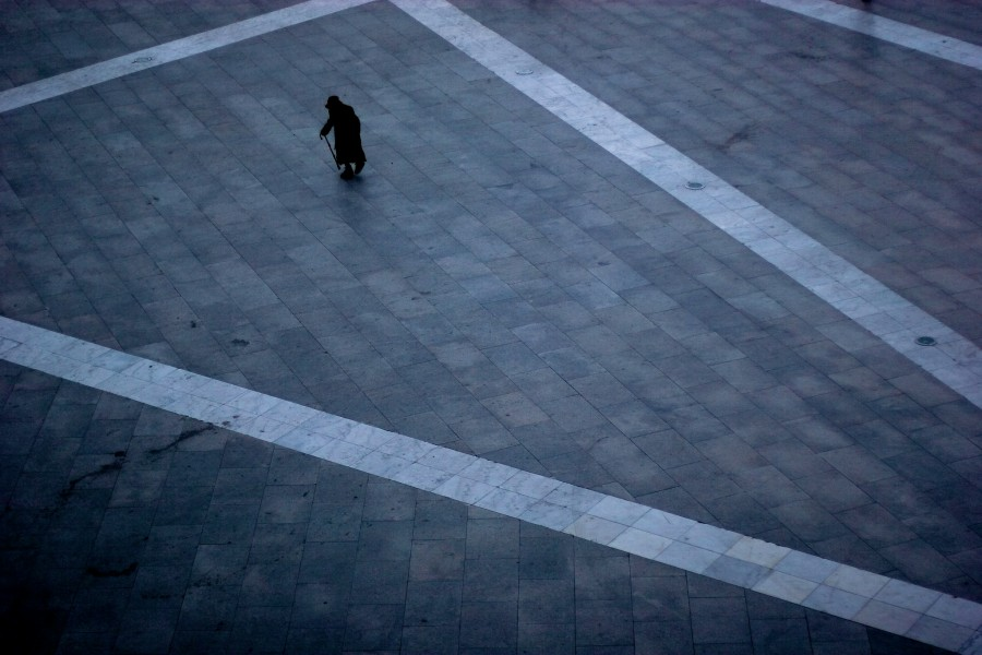 A woman crosses a courtyard on the streets of Lhasa TIbet