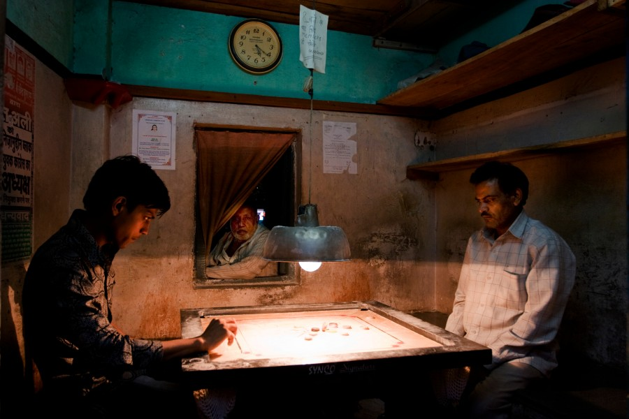Two men play a board game as another looks on in the streets of New Delhi, India
