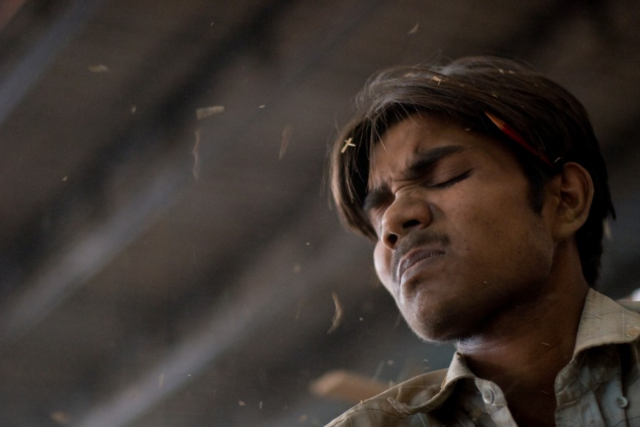 Chips fly into the unprotected eyes of a wood turner at a factory in New Delhi, India