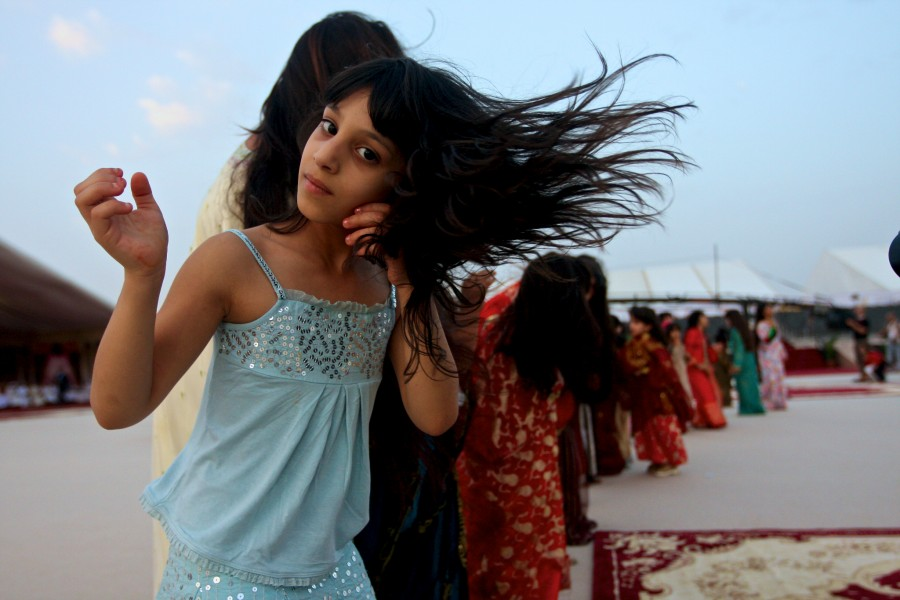 Young girls dance in a line by waving their hair in the air in a traditional dance at a mass wedding in Liwa, United Arab Emirates.
