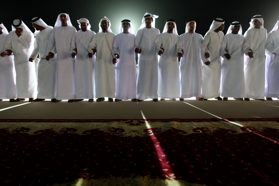 Men stand in line and dance a traditional dance during a mass wedding in Liwa, United Arab Emirates.
