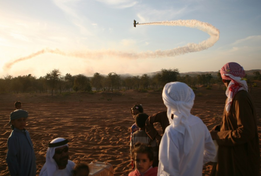 Spectators watch a plan preform stunts and trail smoke in the Al Ain Air Show from the dunes outside of Al Ain Airfield.