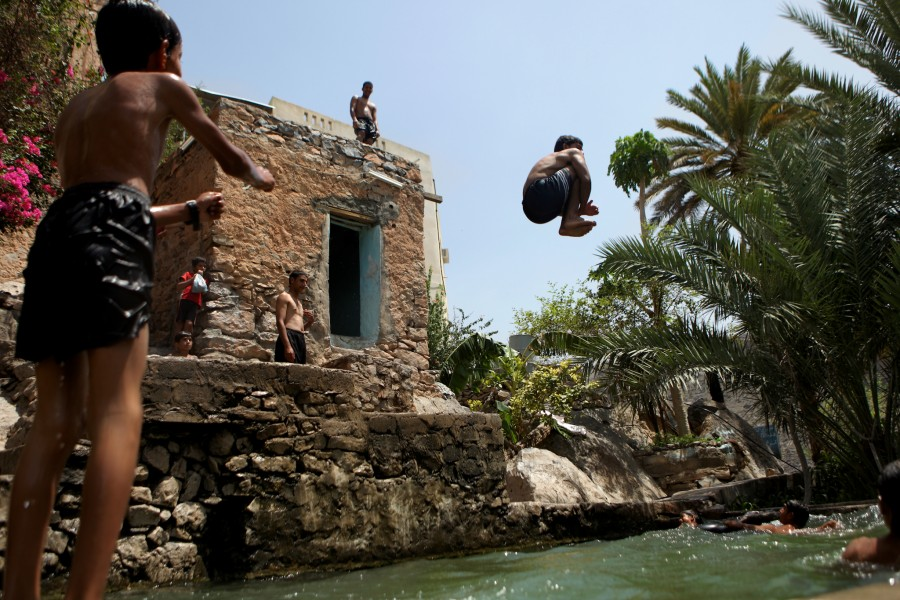 Kids and teens jump from the building ancient buildings and swim in a pool formed by the falaj that supplies water to their village for drinking and farming.