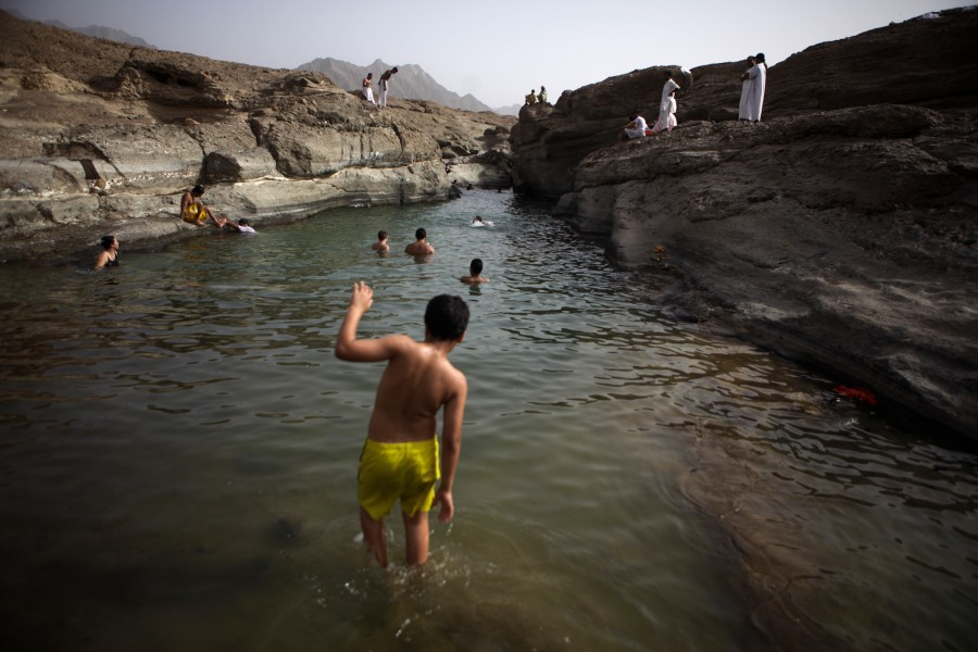 Swimmer wades into the waters at Hatta Pools, a wadi oasis in the desert of the United Arab Emirates.