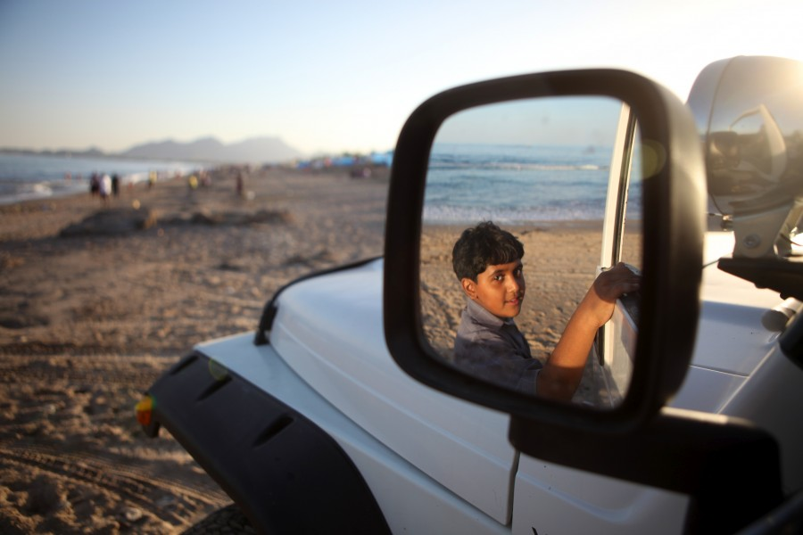 A boy in the rearview mirror of his brother's Jeep.