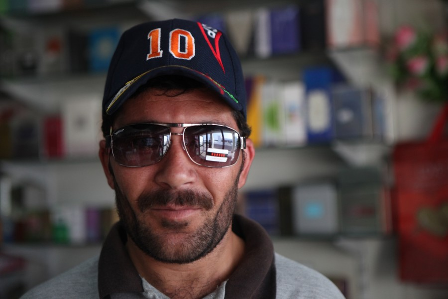 A man wears a pair of sunglasses with the sticker still on.
