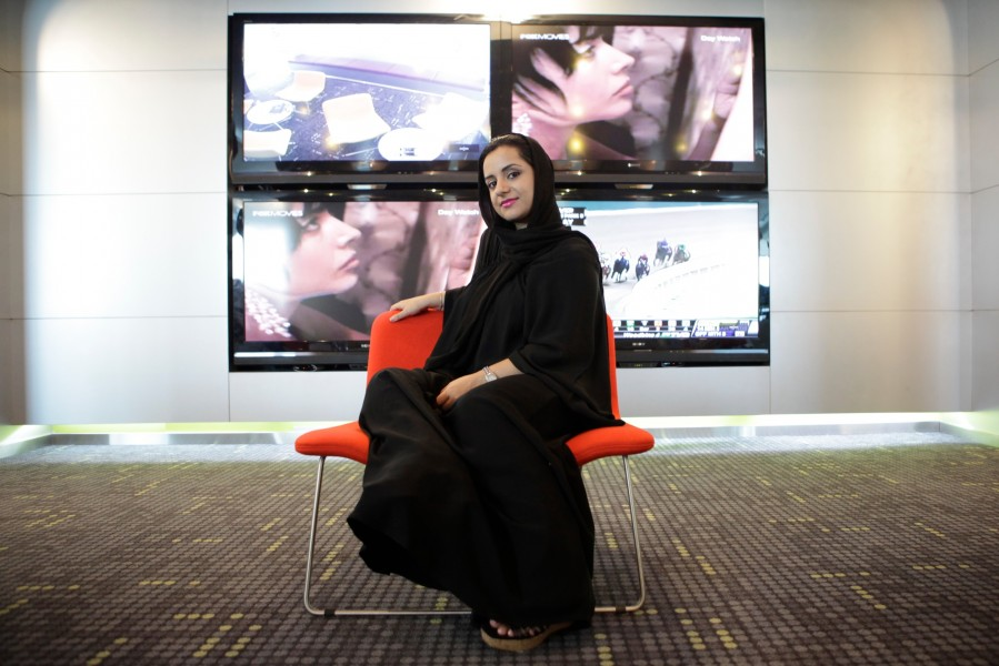 An Emirati woman sits in chair with flatscreen TVs.