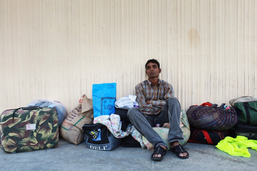 Musabbir Miah from Bangladesh sits with the belongings he could salvage from their building when it cought fire.