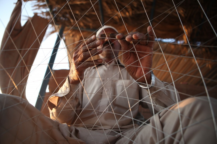 A man weaves wire fishing traps on Delma Island, UAE