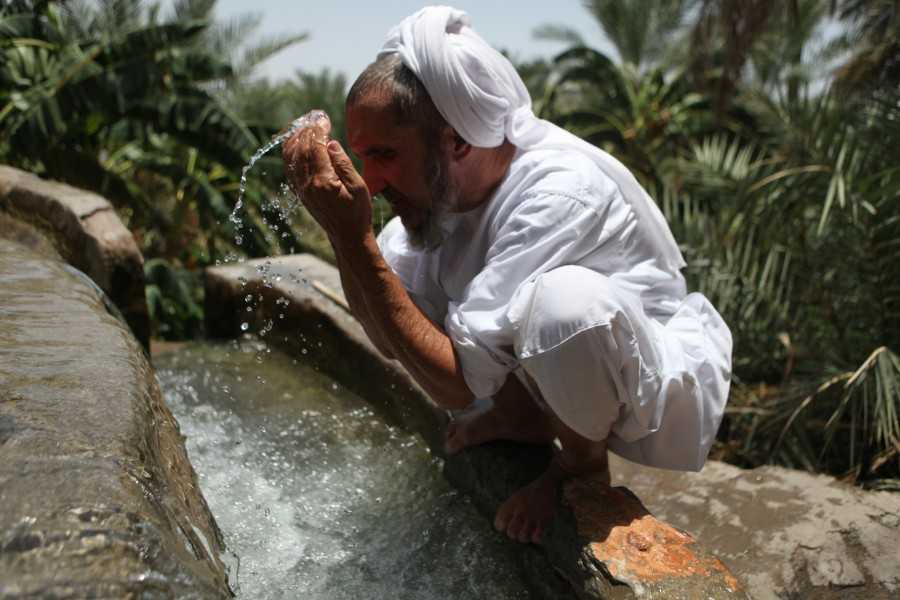 Sulem al Abri washes in the falaj before praying in the mosque in Misfat Oman