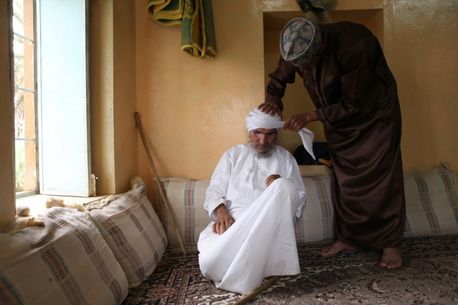 Suleman al Abri has his grandson help dress him before going to mosque in Misfat Oman