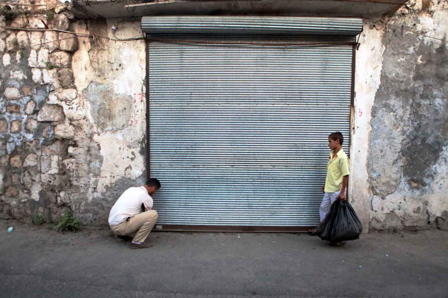 A shopkeeper and his son lock the storefront at the end of the day in Hasankeyf Turkey