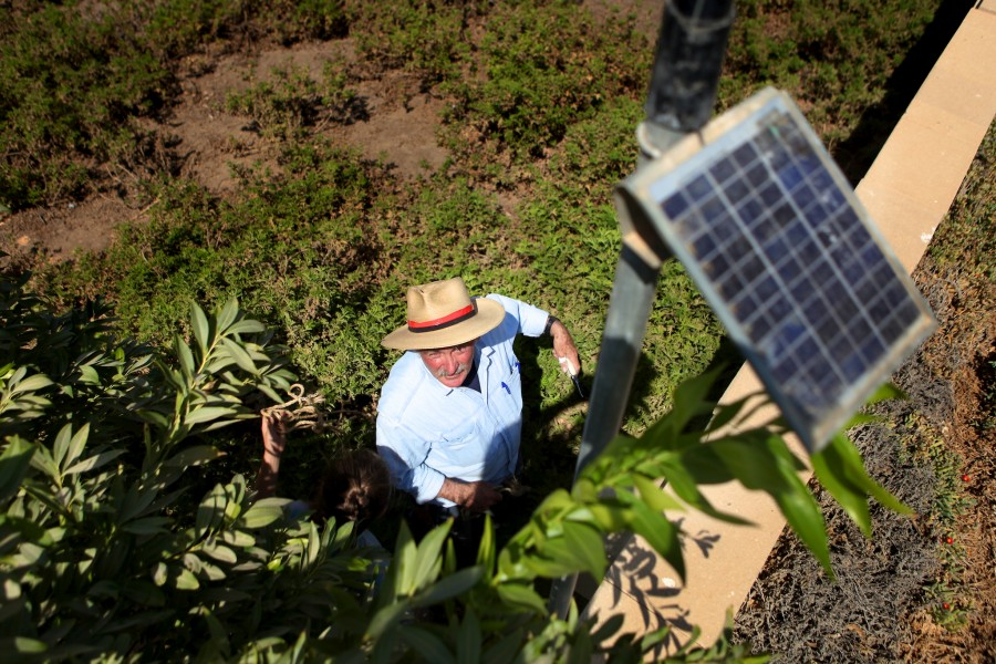 A groundskeeper adjusts a solar powered instrument used for regulating irrigation water